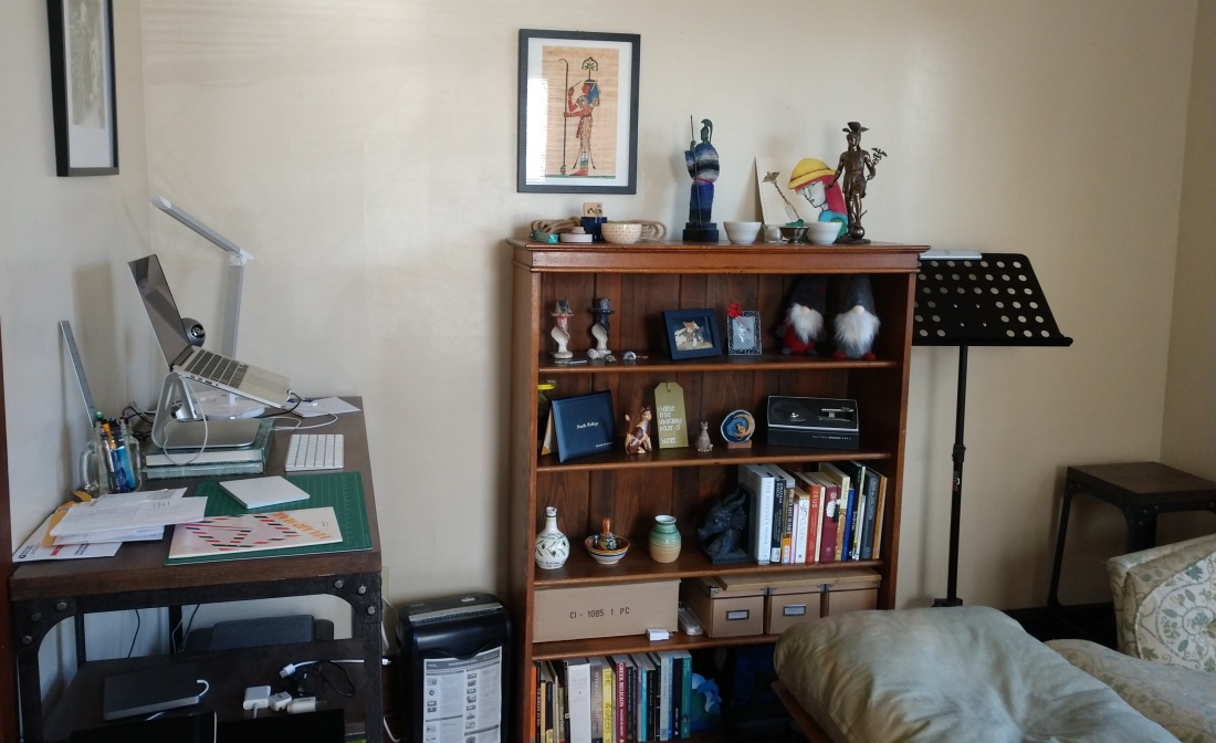 A bookshelf with shrines atop it, with a desk on the left against a perpendicular wall and some soft seating in the foreground