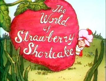 "A giant strawberry with ""the world of strawberry shortcake"" written on it in cursive, Strawberry herself peeking out from behind it"