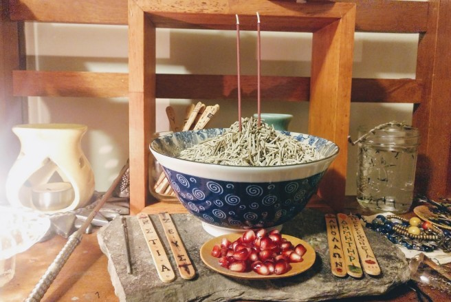Incense burning and pomegranate seeds on my shrine. A candle is lit to the far left, slightly off-image.
