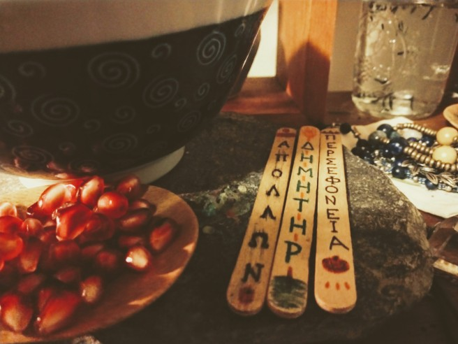 A close-up of the pomegranate seed dish (made of bamboo) and the sticks that have the names of gods on them.