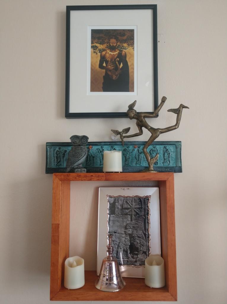 A wall shrine made of a wood square shelf containing sacred images.